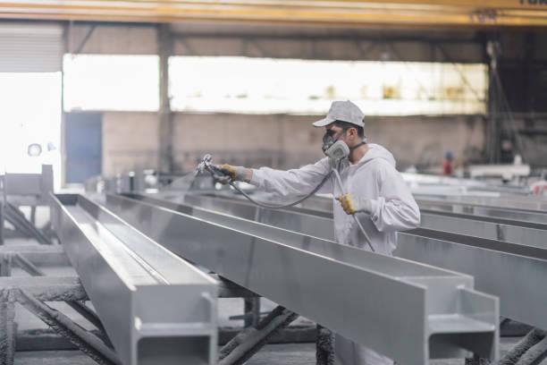 man painting metal in factory